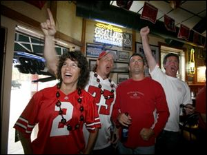 Melisa and Mike Konczal of Chesterfi eld, Mich., Chad Garrison of Maumee, and Mark Kramer of Perrysburg cheer on the Buckeyes at Dale's Bar on Sept. 11.