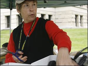 Betty Coleman of Toledo creates ribbons for 'Arlington Midwest,' which will remain on the lawn of the Lucas County Courthouse until Oct. 10.