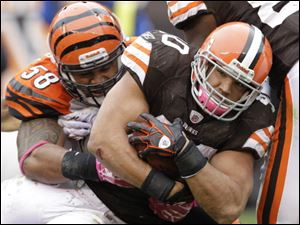 Browns running back Peyton Hills fights for yards against Bengals linebacker Rey Maualuga.