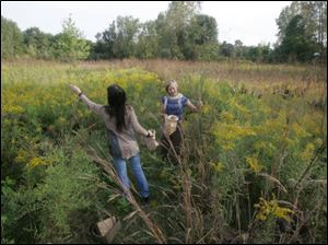 Stephanie Saba, left, and Heather Clendenin, Members of Wild Ones, gather seeds in Michelle Grigore's prairie.