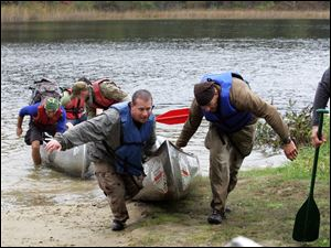 Paramedic Todd Metcalf, left, of Northwood and team member Tim McCormick of Lyons, Ohio, drag their canoe out of Pickerel Lake during the Midwest MedWAR in Pinckey, Mich.