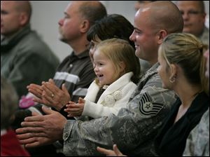 Tech Sgt. Shawn Doogs of Bloomdale, Ohio, with daughter Olivia on his lap, cheers during the ceremony. To his left is his wife, Tara; to his right are his parents, Ron and Jackie.
