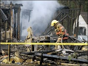 Firefighters work at the scene of a house fire that killed five people in Bartles, Ohio, on Monday. Seven other people were injured in the fire in rural southern Ohio.