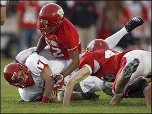 Bedford quarterback Jared Kujawa is brought down after a long run by Monroe's Reggie Allen, top, and Jakup Macmullen.