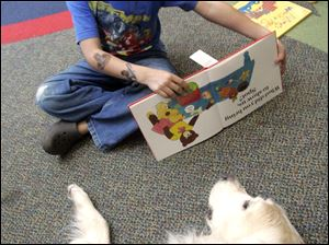 Kyle Roessle, 6, of Temperance reads to Finnie.