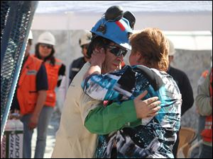 Johnny Barrios Rojas, 50, embraces his mistress Susana Valenzuela after his rescue. While he was trapped underground, his wife found out about his girlfriend when the two met at Camp Hope. His wife was not there to greet him.