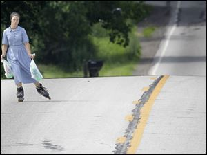 An Amish girl uses inline skates as she carries groceries in Middlefield, Ohio.