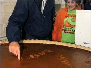 The Republican candidate for governor, John Kasich, writes his name in a pumpkin pie at a Circleville bakery that touts the treat as the world's largest. He plans to campaign in Toledo on Tuesday.