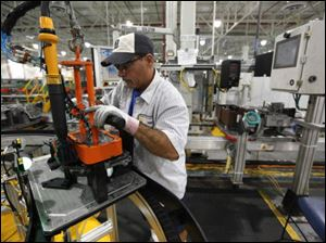 John Backers assembles a six speed transmission Monday at the Ford Motor Co. Van Dyke Transmission Plant in Sterling Heights, Mich.