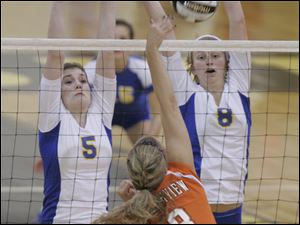Katie McKernan (5) and Maggie Burnham (8) put up a wall against Southview's Kelsey Blankerts in last night's second match.