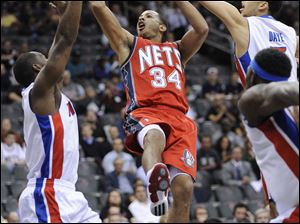 Detroit's Rodney Stuckey, left, and Austin Daye attempt to stop the New Jersey's Devin Harris.