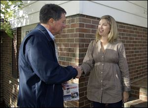 John Kasich greets Nicole Carrier while campaigning in Worthington. 'Just when we think we've knocked on the last door, we're going to knock on a few more doors,' Mr. Kasich said.