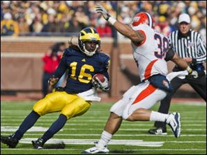 Denard Robinson (16) tries to evade Illinois linebacker Ian Thomas (38) during the second quarter of the game, Saturday.