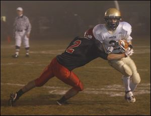 Bedford's Tyler Hooven tackles Grosse Point South's Matthew Reno in Friday night's playoff game.