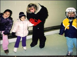 In this photo from 2003, Monica Jablonski is on the ice with Sarah, left, Cate, and Matthew Orchard. A native of British Columbia, Mrs. Jablonski, 71, of Springfield Township taught the basics of ice skating to multiple generations of local youngsters.
