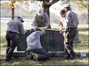 Bob Sobiniak, left, Tim Evans, Roger Wilhelm, Bryan Lorann, and Terry Rankin install a headstone at Toledo's Historic Woodlawn Cemetery. At least 50 markers were toppled there in March, 2009.