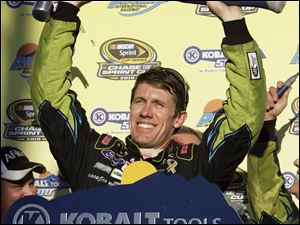 Carl Edwards holds up the trophy for winning Sunday's race at Phoenix International Raceway.