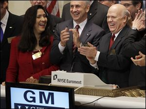 GM CEO Dan Akerson, right, and other officials applaud after ringing a bell to open the New York Stock Exchange. The sounds of a revving motor followed.
