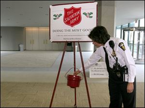 Toledo police Capt. Diana Ruiz-Krause contributes to the Salvation Army red kettle after the kickoff Thursday in the lobby of the Fifth Third Center in downtown Toledo. Bell ringers will be out in force this holiday season to collect $50,000 more than last year's $470,000.