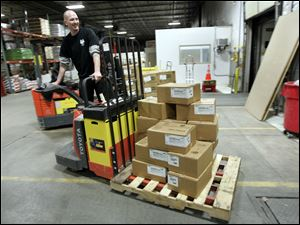 Bill Meier moves a pallet of supplies to be shipped out of the company's distribution center