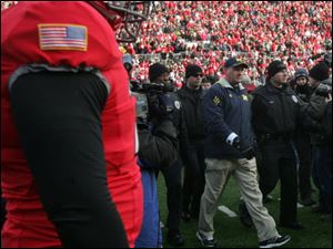 Security officers escort coach Rich Rodriguez off the field at Ohio Stadium Saturday as the Buckeyes won 37-7. Rodriguez is now 6-18 in the Big Ten.