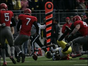 Michigan's Denard Robinson fumbles to stop an early scoring opportunity. The Wolverines turned the ball over three times.