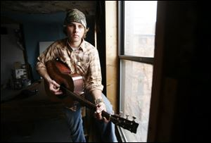 Michael Corwin strums a guitar in his downtown apartment.
