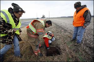Beverly Bovee, left, Roger Robinson, Jr., Brandy Daley, and Michelle Van Dam check a drain along County Road 19 just south of Morenci.
