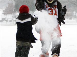 Frieda the Falcon, one of Bowling Green State University's mascots, squares off with Logan McGuire, 9, of Perrysburg in a snowball fight outside of Anderson Arena.
