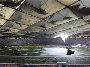 Snow breaks through the roof of the Metrodome in Minneapolis. No one at the stadium was hurt Sunday, but the Vikings' Monday night game against the New York Giants will be moved to Ford Field in Detroit.