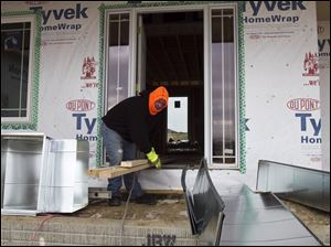 A contractor carries heating ducts to a ho