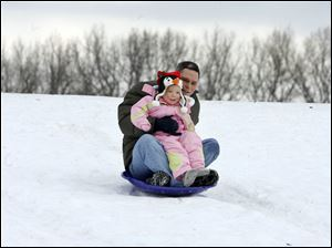 SLUG:  ROV christmassled                          12/25/2010 The Blade/Amy E. Voigt                           Toledo, Ohio   CAPTION:  Chris Kelsey, from Toledo, and his daughter Harmony Kelsey, 2, zip down the hill on the sled Kelsey got for Christmas in Highland Park on December 25, 2010.
