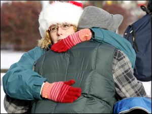 Cindy Nearhood gives a hug, which were distributed in abundance along with the razors, toys, food, and clothing outside the Main Library. Another volunteer, Jennifer Black, wore a 'Free Hugs' apron as she passed out dozens of banana-and-chocolate-chip muffins.
