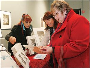 "UT student Susan Mitchell, left, speaks with Kathy Shanteau and Pam Rehkopf at The University of Toledo Department of Art ""A Winter's Sale."""