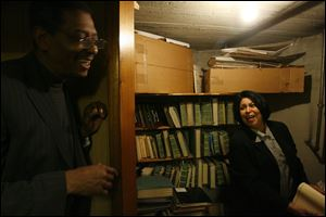 Robert Smith, president of the African American Legacy Project of Northwest Ohio, and Sheryl Riggs of Dale-Riggs Funeral Home look over records in the funeral home's basement. The want to put the information on the Web and in Legacy Project offices