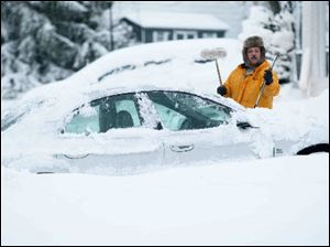 Howard Slovin of Hockessin, Del., digs his car out of the snow in his driveway.