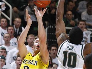 UM's Zack Novak shoots a 3-pointer over MSU's Delvon Roe.