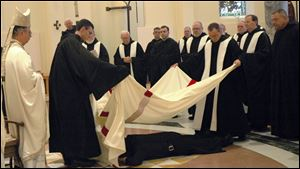 Brother Francis, prostrate on the church floor, is covered with a white-and-red pall used in monastic funerals to symbolize the death of his former self as Craig Wagner.