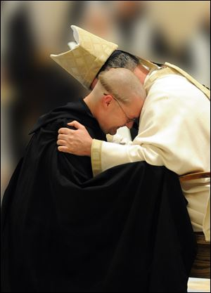 Newly professed monk Brother Francis de Sales Wagner is embraced by Archabbot Justin DuVall.
