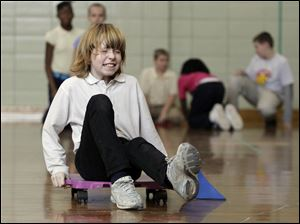 Delani Fuller, a Walbridge Elementary student, rolls in a relay race that requires problem solving with geometric shapes and joining in cooperative learning as well as aerobic physical activity.