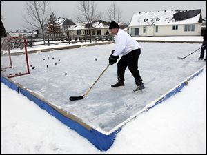 Bob Felser, foreground, plays hockey on his homemade backyard skating rink in Sylvania Township.