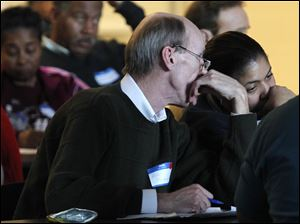Alan Fosnaugh of Robinson Middle School whispers to a neighbor as they listen to the plan put forward by the Toledo Public Schools.