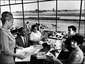 Hostess Irma Lichtenwald greets Mr. and Mrs. Sylvester Hechura and Mr. and Mrs. Jerry Monalian on July 7, 1967, at Raceway Park as the couples prepare to enjoy a meal in the Turf Club with an open view of harness racing on the track.