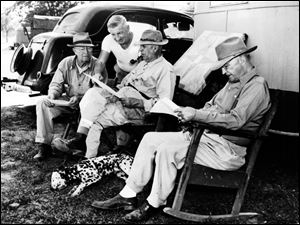 Looking over the race forms for a Sept. 21, 1947, race at Fort Miami include Frank Morris of Celina, Ohio, Jimmie Carroll of New York City, and Harry Gray and Billy Morrow, both of Toledo. Morrow's dog Killey, an 8-month-old Dalmation lying next to his rocking chair, is a companion of the horse Duke of Kent.