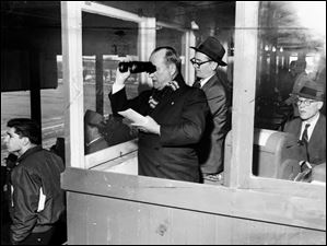 Chart-caller J.J. Hahn peers through field glasses at the track as Tom Mulligan stands nearby and Harland Smith, right, sits at the Teletype machine in the call booth at Maumee Downs.