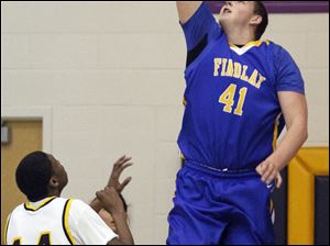 C.J. Gettys (41), a 6-foot-10 junior, lays up 2 points for Findlay against Whitmer's Franklin Lindsey (14).