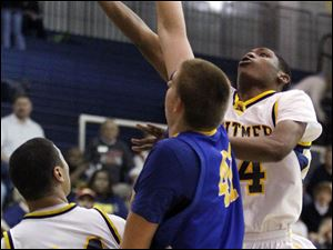 Whitmer's Franklin Lindsey (14) lays up a shot against Findlay's C.J. Gettys (41). Lindsey would give the Panthers a game-high 13 points.