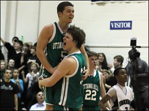 J.J. Buckey (5) jumps into the arms of Ottawa Hills teammate Lucas Janowicz as the Green Bears celebrate a 45-38 win over Maumee Valley.