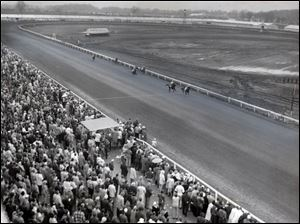 The crowds at Raceway Park watch horses come down the home stretch on April 4, 1960. Thoroughbred racing was expensive to maintain and more vulnerable to weather, such as creating soft spots in the track, so by 1973 Raceway Park was offering only harness racing. The sulkies were still circling the track there in 2011.