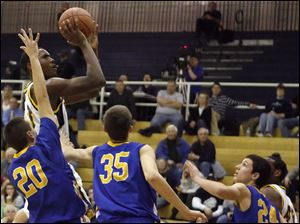Whitmer's Nigel Hayes (23) shoots over Findlay defenders in a non-league high school boys basketball game Feb. 16, 2011, in Toledo, Ohio.